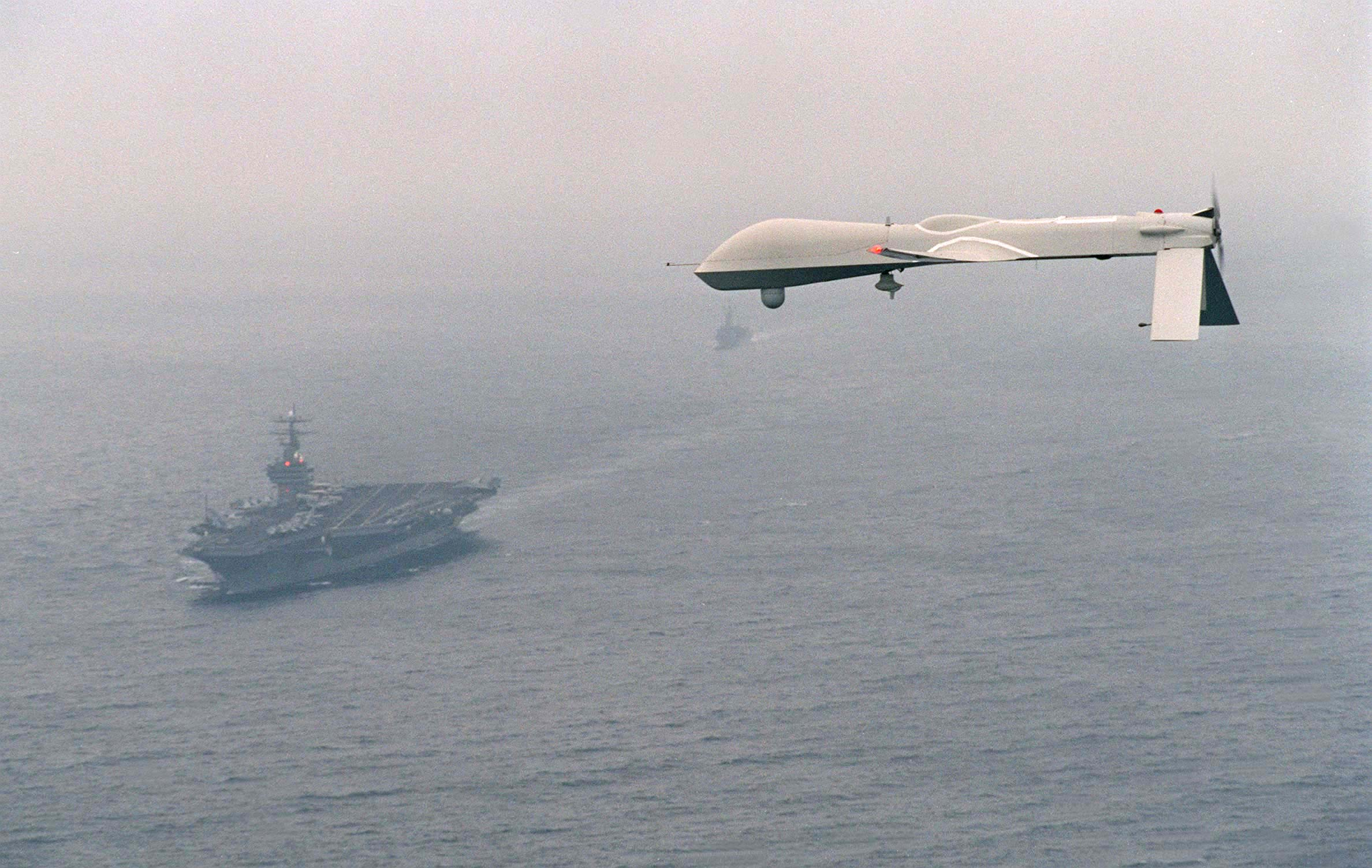 "THE PREDATOR UNMANNED AERIAL VEHICLE (UAV) FLIES ABOVE USS CARL VINSON (CVN 70) ON A SIMULATED NAVY RECONNAISSANCE FLIGHT HEADED BY COMMAND CARRIER GROUP ONE ON DECEMBER 5, 1995, ABOUT 100 MILES OFF THE SAN DIEGO COASTLINE. THE FLIGHT IS THE PREDATOR'S FIRST MARITIME MISSION WITH A CARRIER BATTLE GROUP; PROVIDING ""NEAR REAL-TIME"" INFRARED AND COLOR VIDEO TO THE SHIP DURING ITS FLIGHT. THE PREDATOR, LAUNCHED FROM SAN NICHOLAS ISLAND 0FF THE SOUTHERN CALIFORNIA COASTLINE, IS CAPABLE OF OVER 50 HOURS OF NON-STOP FLIGHT AND IS OPERATED BY A JOINT ARMED SERVICES DETACHMENT. THE DETACHMENT CONSISTS OF A CREW OF MILITARY PILOTS, TECHNICIANS, OPERATORS AND ANALYSTS. THE NAVY'S PLANS FOR THE PREDATOR IN FUTURE EXERCISES AND OPERATIONS INCLUDE SHIP RECONNAISSANCE, BATTLE-DAMAGE ASSESSMENT, AND SEARCH AND RESCUE MISSIONS. PREDATOR HAS A WINGSPAN OF 48.4 FEET, A LENGTH OF 26.7 FEET AND WEIGHS APPROXIMATELY 1500 POUNDS WHEN FULLY FUELED. COST OF THE AIRCRAFT IS AROUND 3.2 MILLION DOLLARS. AVERAGE SPEED IS APPROXIMATELY 70 KNOTS."